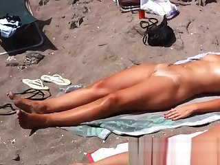 Spy cam shot be required of a hot nudist babe tanning on the beach